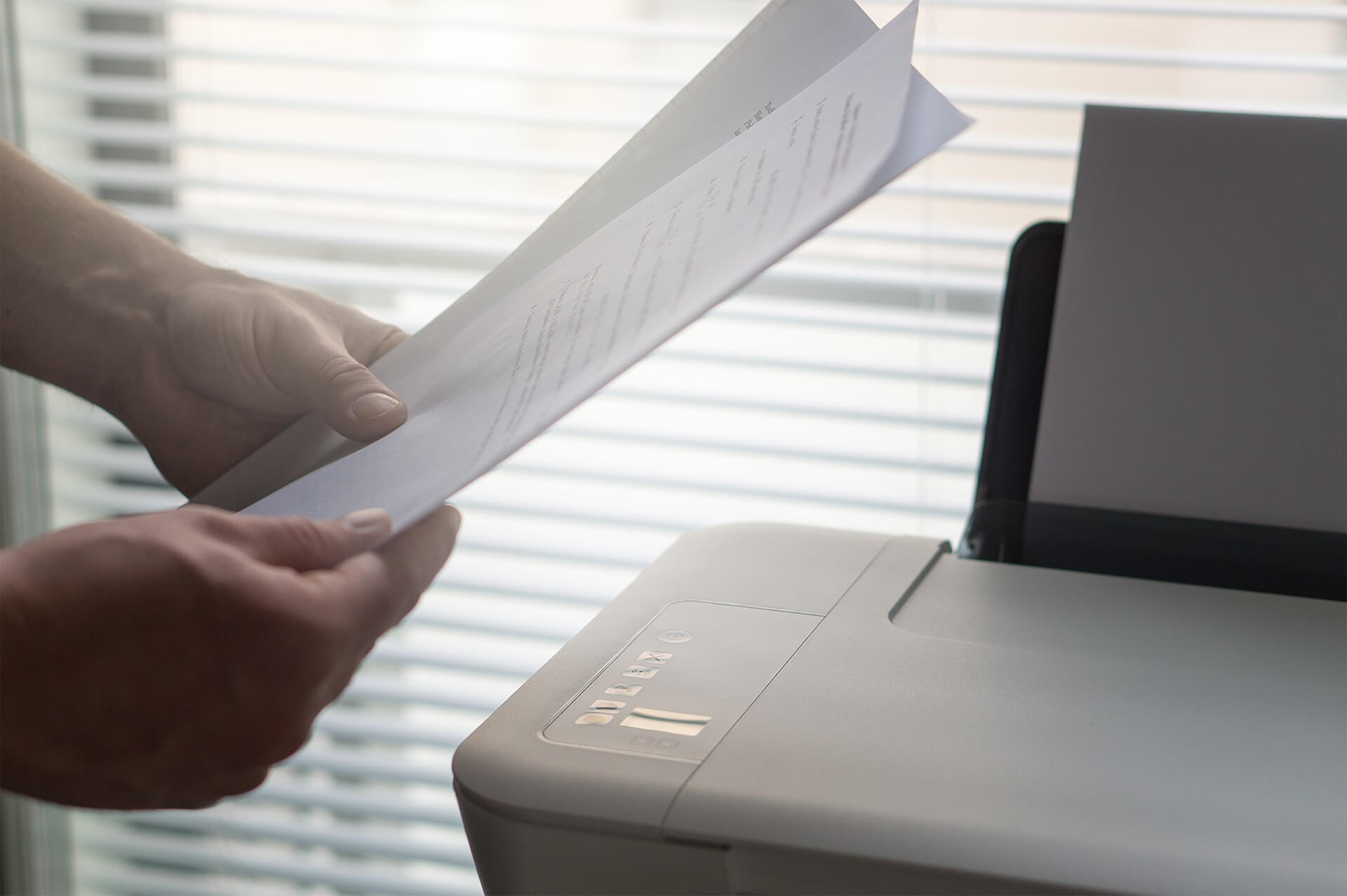 Businessman holds documents in front of the printer