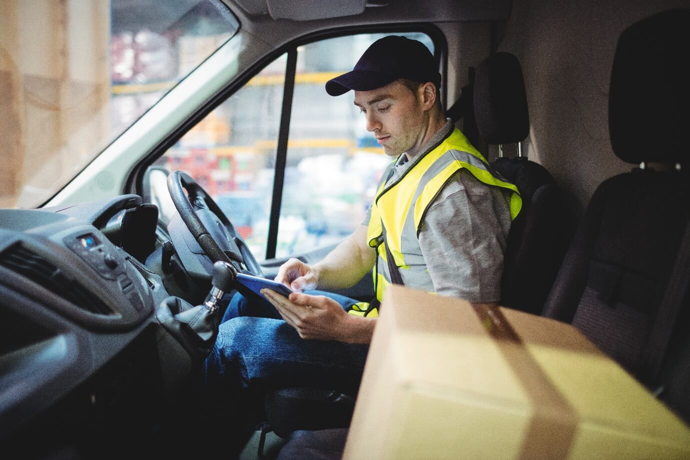 Delivery Driver Sitting In Van Using Digital Tablet